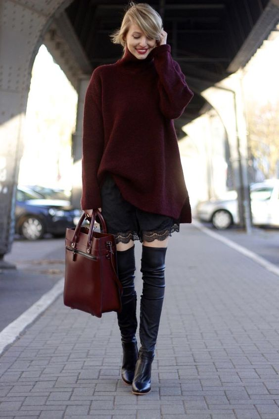 a plum oversized sweater, a large red bag, a black lace dress and black leather boots