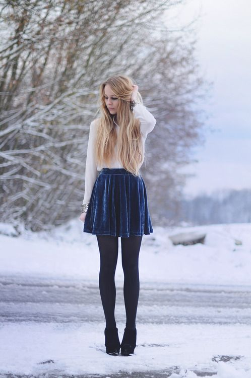 a white blouse, a navy velvet skirt, black tights and booties