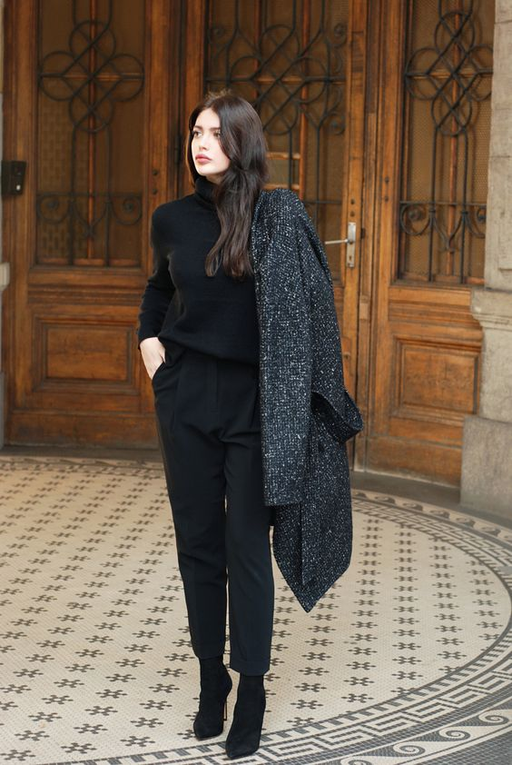 black pants, a black turtleneck, black suede booties and a black printed coat