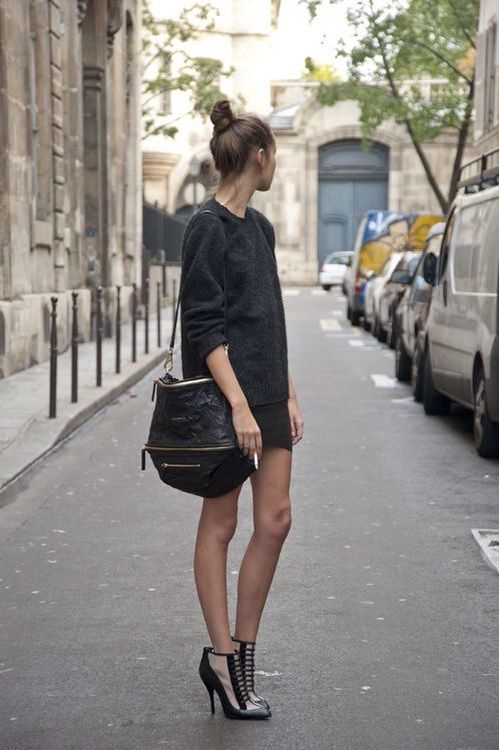 a black sweater, a black mini skirt, creative black and nude boots and a large bag