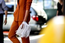 11 a burnt orange suit with a plunging neckline, white sneakers and a white fringe clutch for special occasions