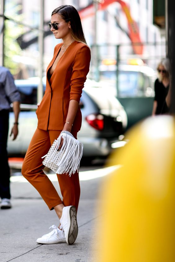 a burnt orange suit with a plunging neckline, white sneakers and a white fringe clutch for special occasions