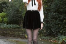 11 a white vintage-style shirt with a black bow and a brooch, a black velvet mini skirt, black tights and boots