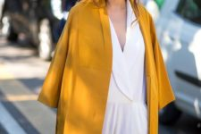 12 a mustard coat on top of a white jumsuit is a chic idea for a special occasion