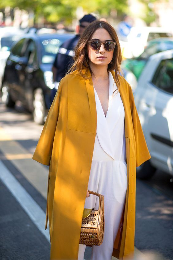 a mustard coat on top of a white jumsuit is a chic idea for a special occasion