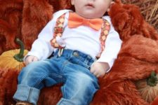 12 a white shirt, plaid orange suspenders, jeans, brown leather shoes and an orange bow tie