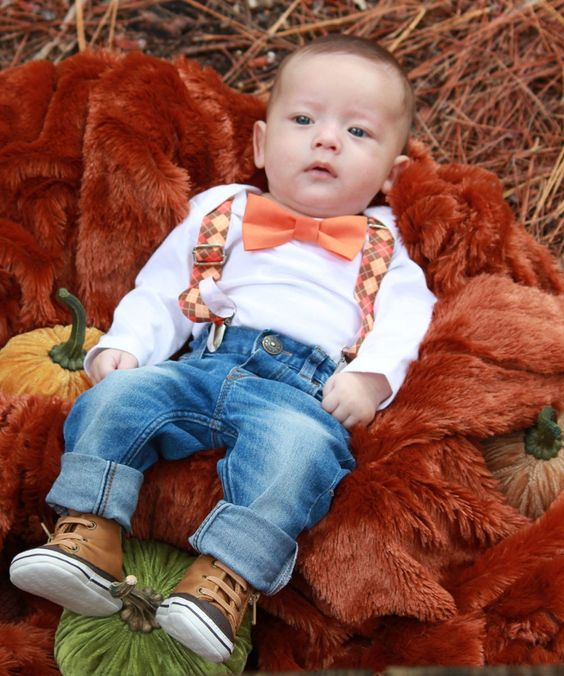a white shirt, plaid orange suspenders, jeans, brown leather shoes and an orange bow tie