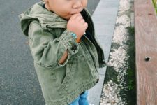 12 distressed blue jeans, white sneakers, an olive green denim jacket and a black beanie