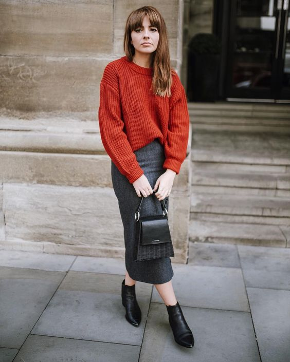 a grey midi skirt, an oversized burnt orange sweater, black booties and a black bag