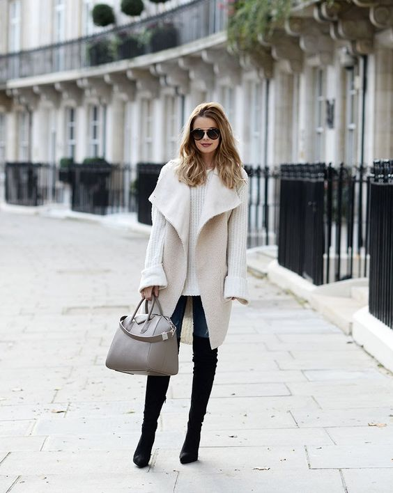 a sheepskin waistcoat, a white sweater, jeans and black tall boots with a grey bag