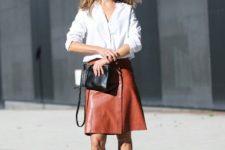 13 a white shirt, a burnt orange leather skirt, grey heels and a black bag