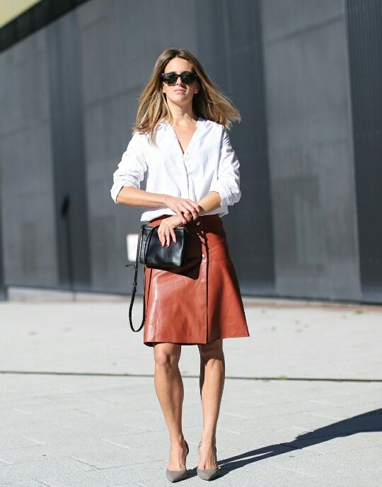 a white shirt, a burnt orange leather skirt, grey heels and a black bag