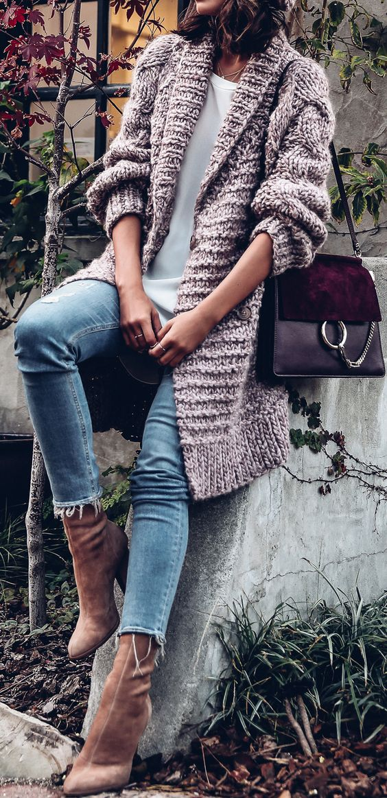 a white top, blue jeans, ocher sock boots and a pink chunky knit cardigan