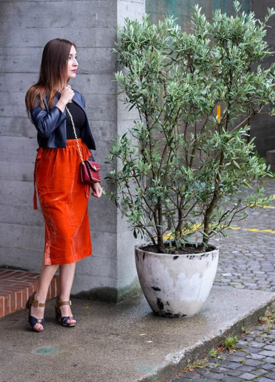 a black tee, a cropped navy leather jacket, an orange midi velvet skirt and vintage inspired shoes
