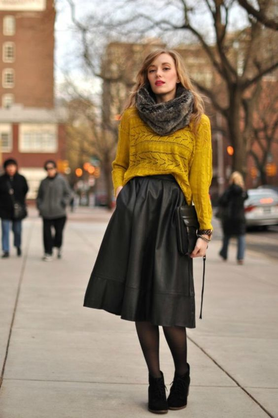 a mustard top, a black A-line midi skirt, suede booties, a faux fur scarf and a clutch