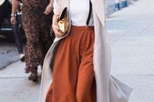 14 a white tee, burnt orange culottes, brown shoes, black suspenders and a creamy coat