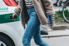 14 a winter look with blue jeans, a striped turtleneck, a shearling coat and purple velvet sock boots