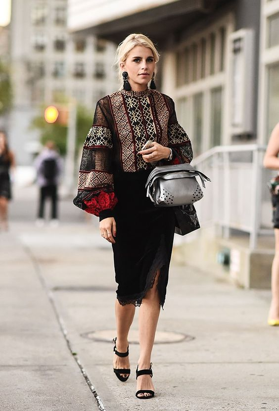 a bold bohemian look with a printed blouse with bell sleeves, a black velvet skirt with a slit, velvet shoes and a silver bag