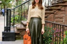 15 a neutral sweater, a green leather midi skirt, an orange vintage bag and plaid flats
