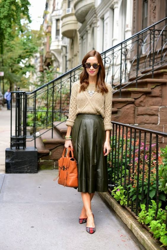 a neutral sweater, a green leather midi skirt, an orange vintage bag and plaid flats