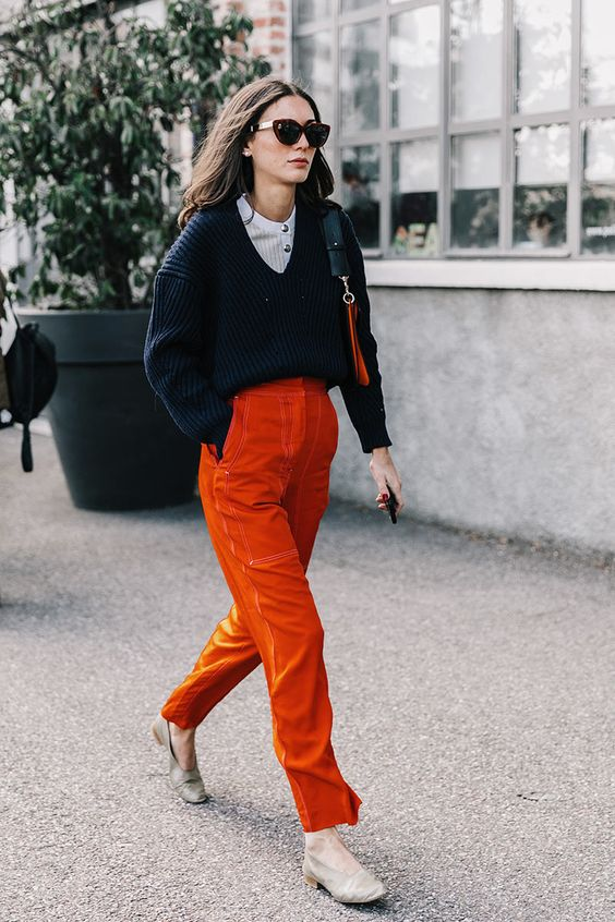 burnt orange velvet pants, a slouchy navy sweater over a white top and nude flats
