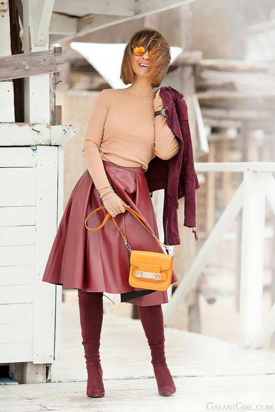 a peachy top, a red leather A-line skirt, burgundy suede boots and a matching jacket