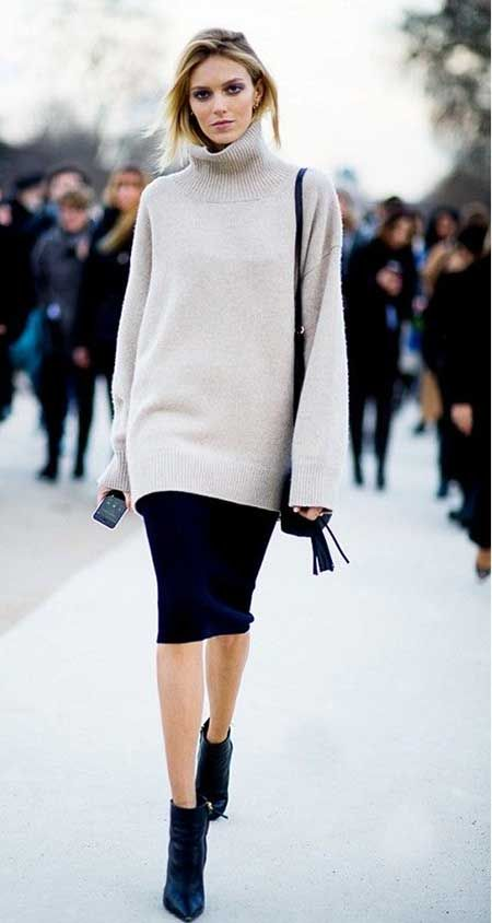 black leather boots, a navy knee skirt, a neutral oversized sweater and a black bag
