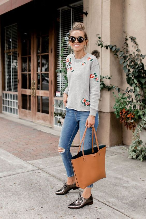 ripped cropped jeans, a floral sweatershirt, flat shoes and an ocher bag