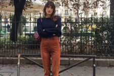 16 vintage-inspired high waisted burnt orange pants, a navy sweater, matching orange shoes and a purple bag