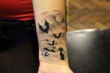 Bats and cat tattoo on the wrist