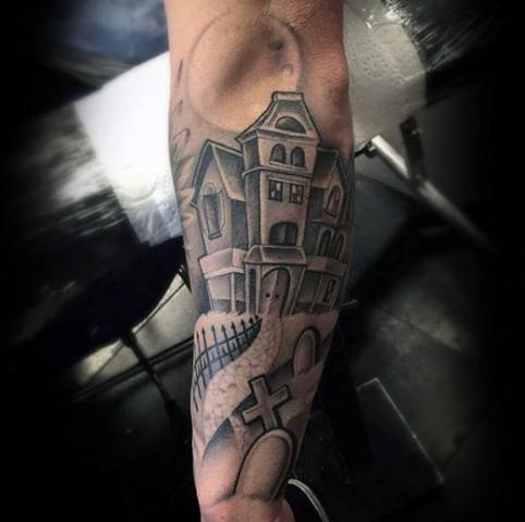 Haunted house and coffin tattoo on the forearm