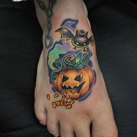 Pumpkin and bat tattoo on the foot