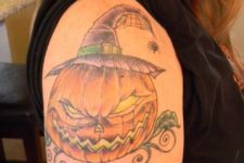 Pumpkin with evil smile, hat and spider tattoo