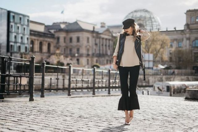 With beige blouse, black leather vest, cap and metallic shoes
