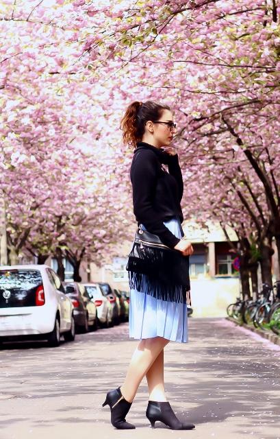 With black blouse, light blue skirt and fringe bag