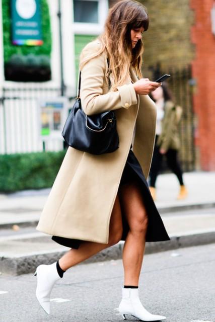 With black dress, beige coat and black bag