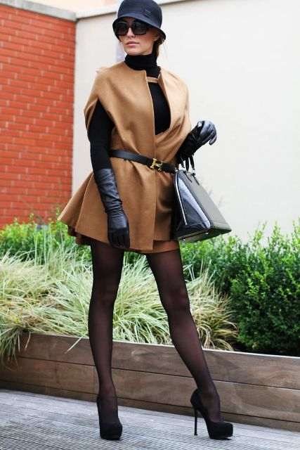 With black hat, camel coat, brown mini skirt, black turtleneck and pumps