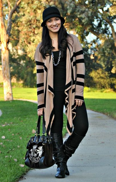 With black shirt, black pants, oversized cardigan, boots and bag