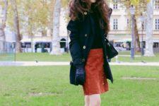 With black shirt, burnt orange suede skirt, black coat and gloves