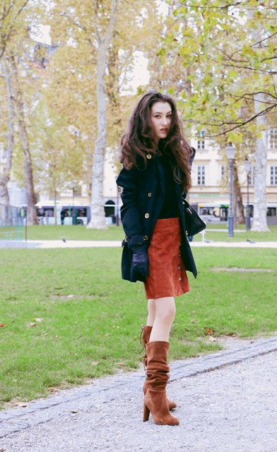 With black shirt, burnt orange suede skirt, black coat and gloves