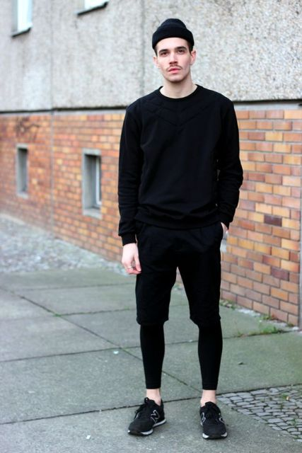 With black sweatshirt, pants and black sneakers
