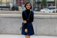 With black turtleneck, blue mini dress and mini bag