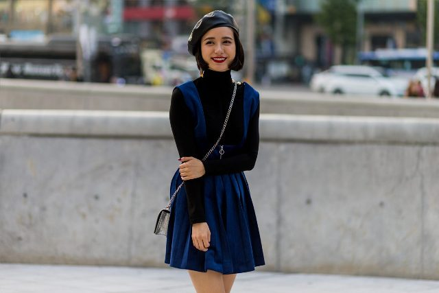 With black turtleneck, blue mini dress and mini bag