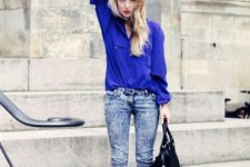 With blue shirt, black shoes and black leather bag