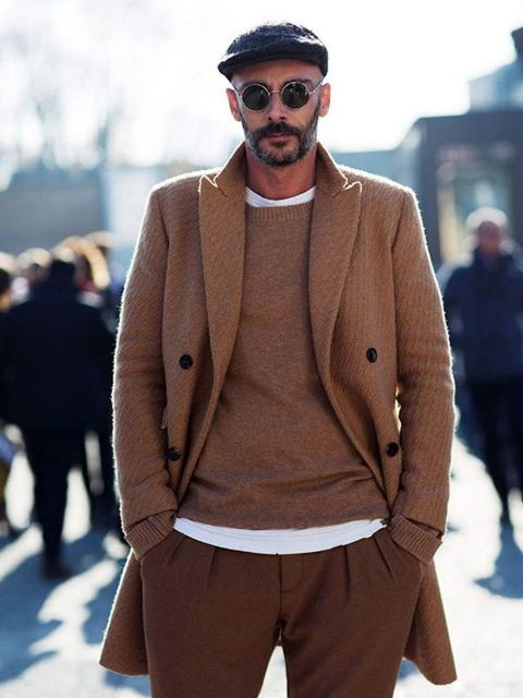 With camel coat, sweater, white t-shirt and brown pants