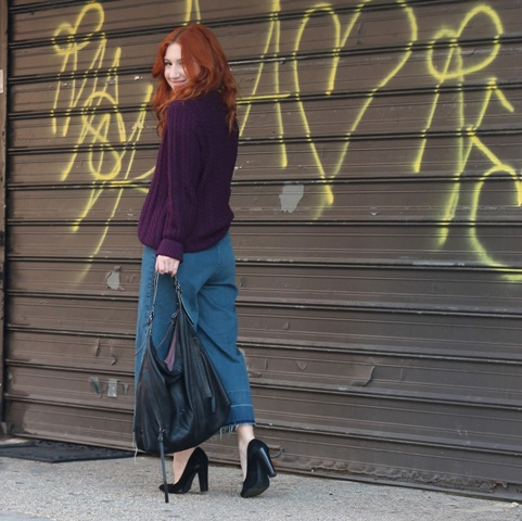 With dark purple sweater, black pumps and tote