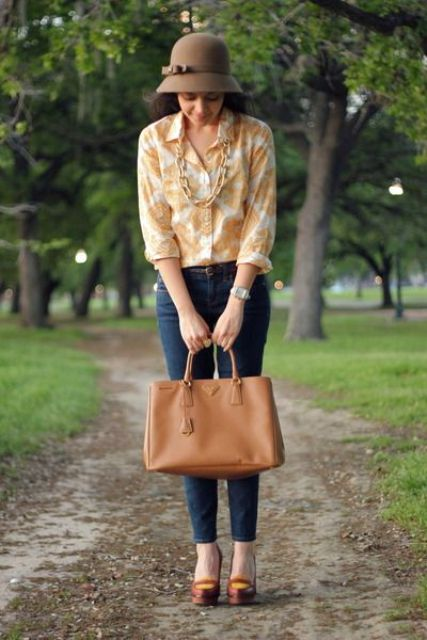 With floral shirt, necklace, jeans, brown shoes and leather bag