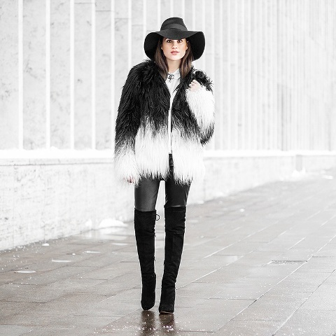 With gray jeans, black high boots and black wide brim hat