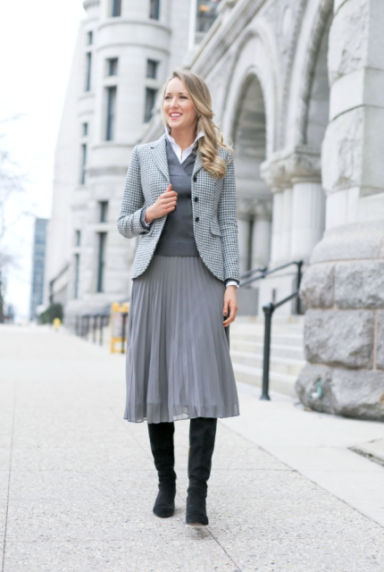 With gray vest, gray midi skirt and black bag