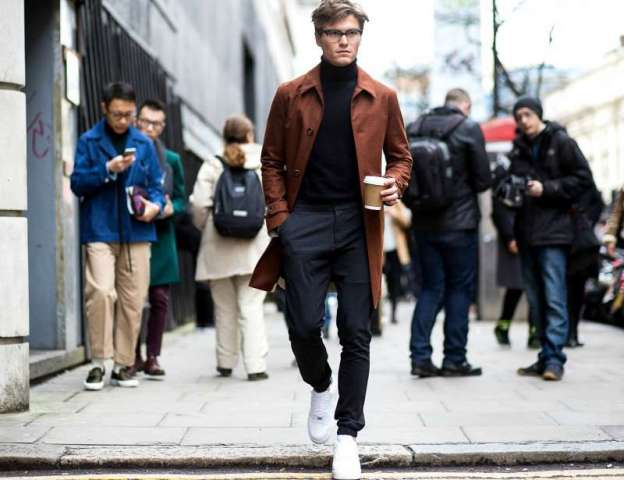 With navy blue pants, white sneakers and burnt orange coat